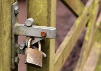 Un lucchetto tiene chiuso un cancello, per simboleggiare l'immobile occupato.