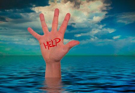 Una mano esce dall'acqua chiedendo aiuto.