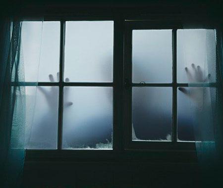 Si intravede una figura inquietante attraverso una finestra appannata.