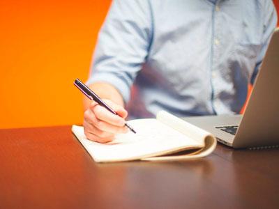 Una persona prende appunti davanti a un computer portatile.