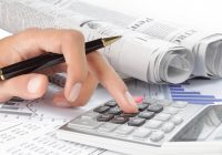 Una mano e una calcolatrice conteggiano spese.