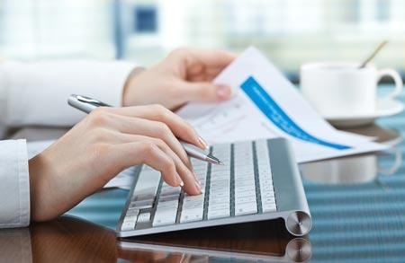 Delle mani alla tastiera per immettere una contabilità