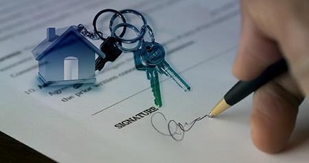 Una mano che firma un documento e vicino un portachiavi con le chiavi dell'immobile comprato