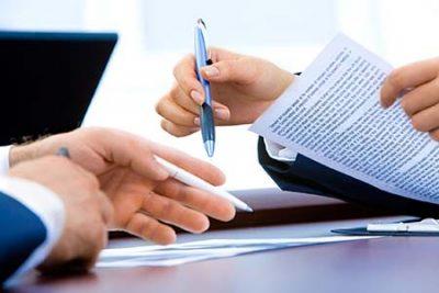 due mani che reggono documenti e penne