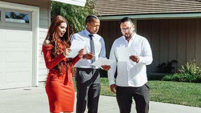 Consulente visiona i documenti con gli acquirenti della casa